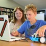 Dunn School Photo #4 - Donna Frost (Chair of the STEM department) helps a student with his robotics project.